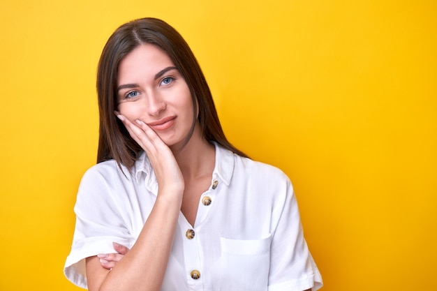 Portrait de jeune fille brune tenant sa joue avec la main, est triste et pense isolé sur jaune