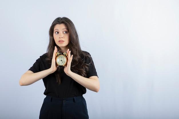 Portrait de jeune fille brune en tenue noire tenant horloge et posant sur fond gris