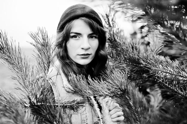 Portrait de jeune fille brune en veste de chapeau et jeans à l'arbre de noël.