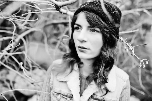 Portrait de jeune fille brune en veste chapeau et jeans à buissons gelés.