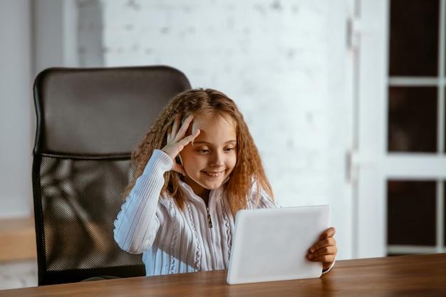 Portrait de jeune fille caucasienne a l'air rêveur, mignon et heureux. regardant vers le haut, assis à l'intérieur à la table en bois avec tablette et smartphone. concept d'avenir, cible, rêve d'acheter, visualisation.