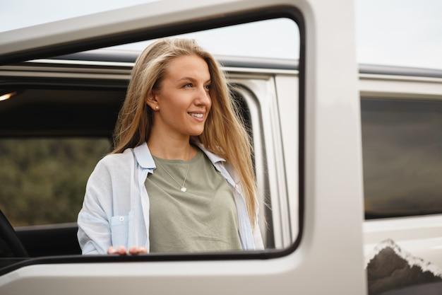 Portrait d'une jeune fille caucasienne heureuse posant près d'une voiture tout-terrain