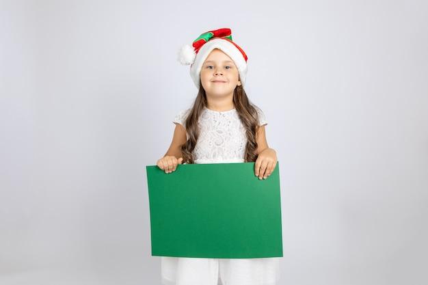 Portrait d'une jeune fille caucasienne souriante en robe blanche et chapeau de gnome de noël tenant une bann vide verte...
