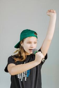 Portrait d'une jeune fille chantant une chanson avec un microphone