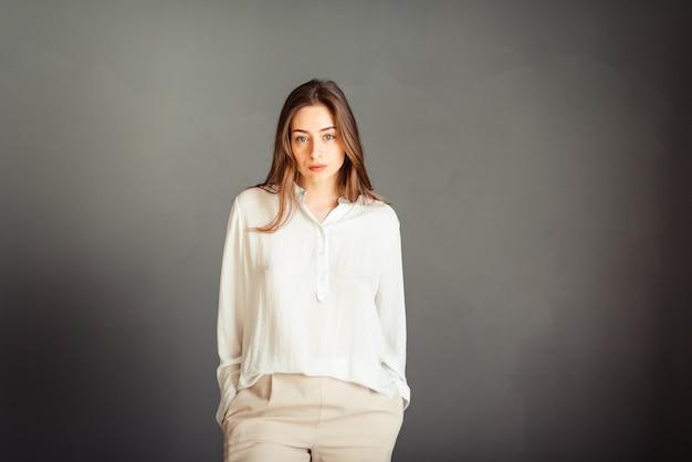 Portrait d'une jeune fille en chemise blanche, regardant droit, les deux mains dans la poche sur un mur gris. pas de retouche. sans maquillage.