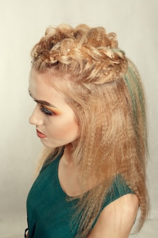 Portrait de jeune fille en chemise verte aux cheveux tressés