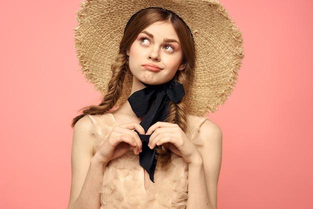 Portrait d'une jeune fille dans un chapeau de paille sur un fond rose émotions gros plan beau visage modèle tresses