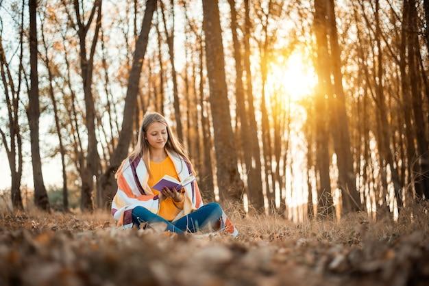Portrait d'une jeune fille dans une forêt d'automne avec un livre contre le soleil couchant
