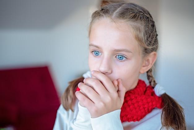 Portrait d'une jeune fille dans un foulard rouge qui tousse dans sa main.