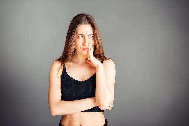 Portrait d'une jeune fille dans un haut noir avec ses cheveux lâches. main près des joues. dent, la mâchoire fait mal. sur un mur gris. sans maquillage, sans retouche.