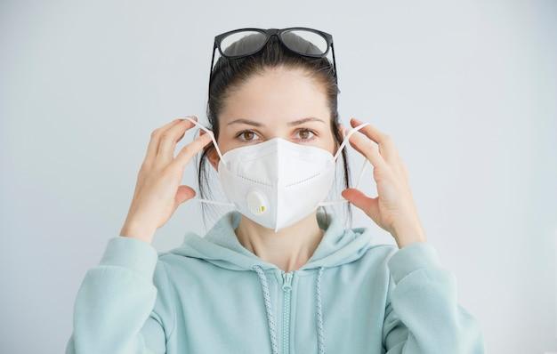 Portrait d'une jeune fille dans un masque médical isolé sur fond de mur blanc. patient de jeune femme, espace de copie