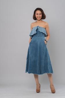 Portrait de jeune fille dans une robe jeans sur gris