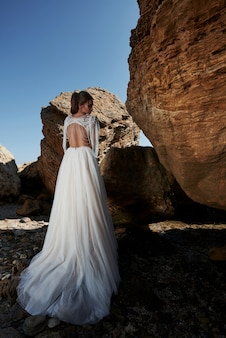 Portrait d'une jeune fille dans une robe magnifique de mariage posant un photographe sur la plage. la mariée est sur les rochers