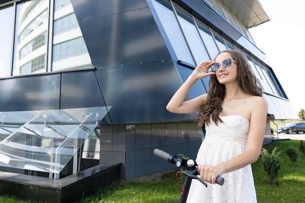 Portrait d'une jeune fille dans une robe avec un scooter électrique sur le fond des bâtiments modernes