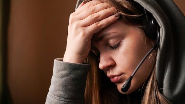 Portrait de jeune fille dans un sweat à capuche et avec un casque travailleur du centre d'appels fatigué