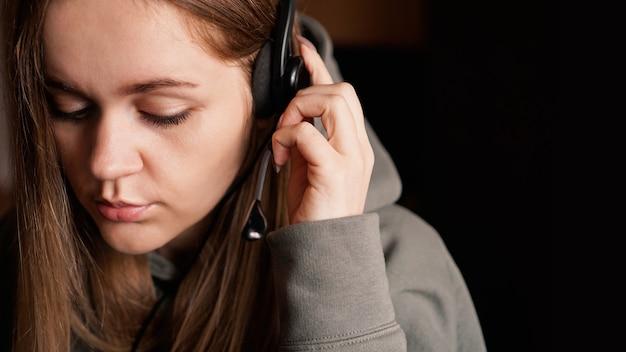 Portrait d'une jeune fille dans un sweat à capuche et avec un travailleur du centre d'appels de casque
