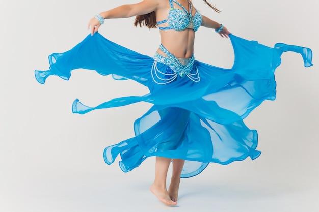 Portrait de jeune fille danseuse du ventre en bleu. isolé sur blanc.