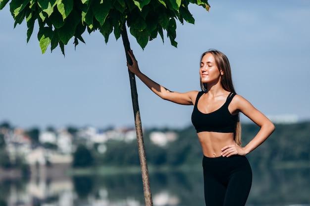 Portrait de jeune fille debout ensuite un arbre avec les yeux fermés en plein air.