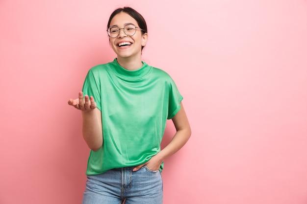 Portrait d'une jeune fille décontractée heureuse debout isolée sur un mur rose, riant