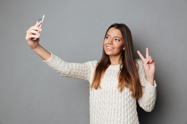 Portrait d'une jeune fille décontractée en pull montrant un geste de paix