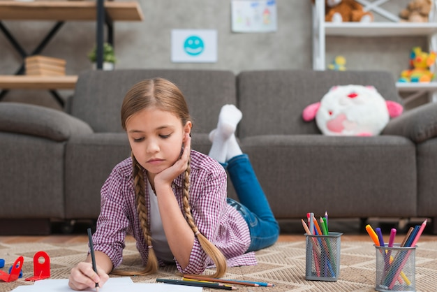 Portrait d'une jeune fille dessinant au crayon de couleur sur papier
