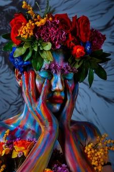 Portrait d'une jeune fille dont le visage est peint de peintures colorées dans une couronne de fleurs. sur les traces de frida kahlo