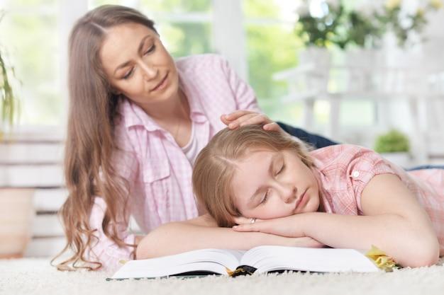 Portrait de jeune fille dormant sur un livre pendant que sa mère s'occupe d'elle