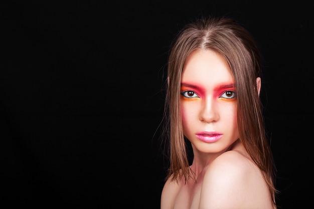 Portrait d'une jeune fille avec du maquillage rose sur fond noir