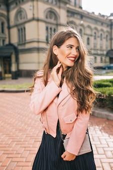 Portrait de jeune fille élégante aux cheveux longs posant sur rue
