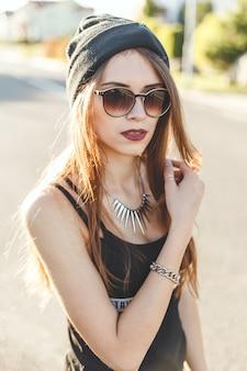 Portrait d'une jeune fille élégante hipster vêtue de bonnet foncé et lunettes de soleil
