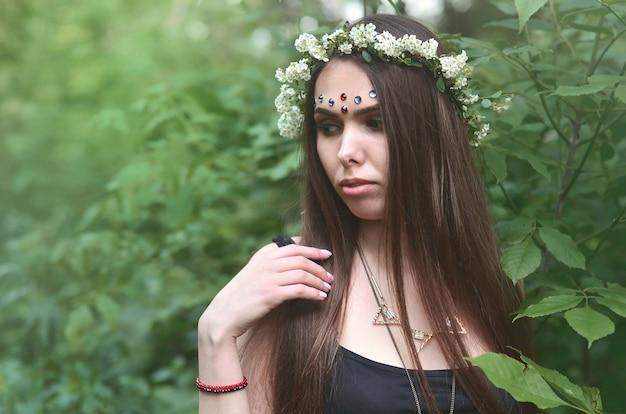 Portrait d'une jeune fille émotive avec une couronne de fleurs sur sa tête et des ornements brillants sur son front