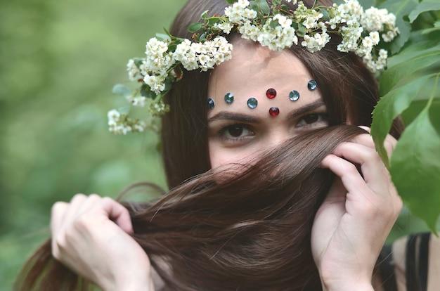 Portrait d'une jeune fille émotive avec une couronne florale sur elle