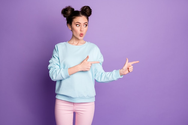 Portrait de jeune fille étonnée pointer l'index copyspace démontrer des publicités à prix réduit choisir des conseils porter un pantalon isolé sur fond de couleur violette