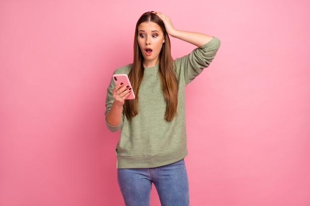 Portrait de jeune fille étonnée utiliser un téléphone portable impressionné sans voix