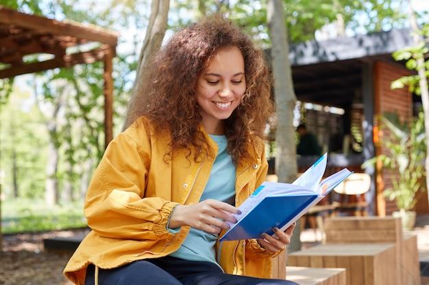 Portrait de jeune fille étudiante bouclée à la peau sombre implantée sur une terrasse de café, vêtue d'un manteau jaune, sourit largement et aime étudier.