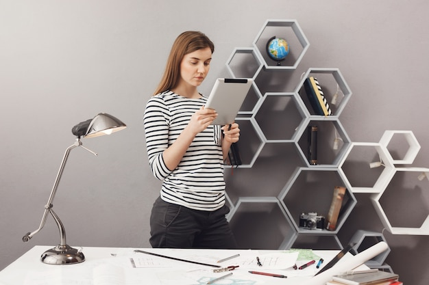 Portrait de jeune fille étudiante gai beau concepteur aux cheveux bruns debout près de table, envoyer des sms avec l'équipe sur tablette numérique.