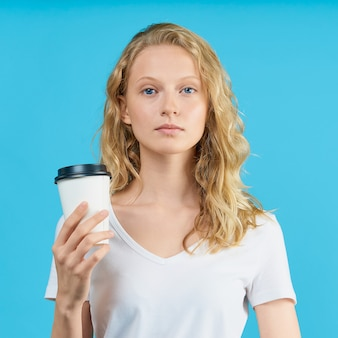 Portrait de jeune fille étudiante avec une tasse de café sur un mur bleu vif de couleur.
