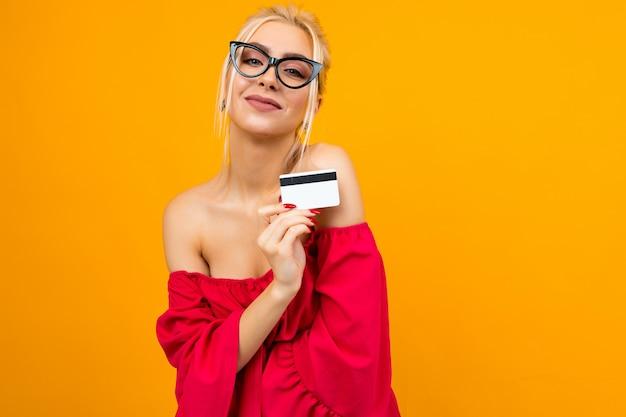 Portrait d'une jeune fille européenne dans une robe rouge avec une carte de crédit avec un modèle pour une banque sur une affiche avec copie espace