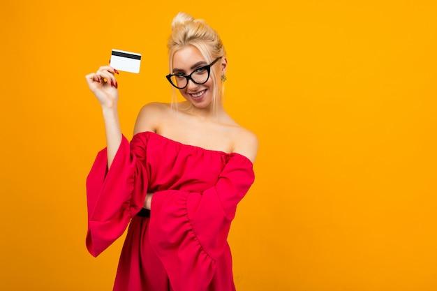 Portrait d'une jeune fille européenne dans une robe rouge avec une carte de crédit