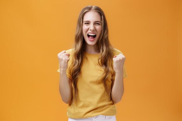 Portrait d'une jeune fille européenne heureuse et gaie avec de longs cheveux ondulés naturels soulevant des fi...