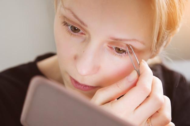 Portrait d'une jeune fille européenne qui épile les sourcils, se regarde dans le miroir. gros plan, visage femme, épiler, poils faciaux mise en forme et soin des sourcils.