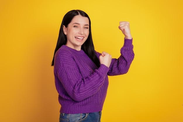 Portrait de jeune fille excitée leva les mains les poings en l'air pour célébrer le succès de la victoire isolée sur fond de couleur jaune