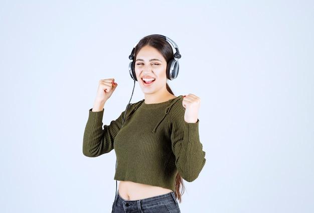Portrait de jeune fille expressive écoutant de la musique et dansant.