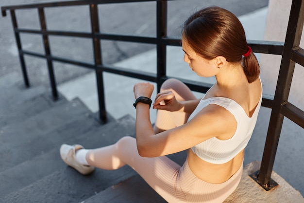 Portrait d'une jeune fille fitness assise dans les escaliers à l'extérieur et vérifiant la quantité de calories brûlées après l'entraînement, femme aux cheveux noirs en haut blanc et leggins beiges.