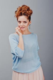 Portrait de jeune fille frisée aux cheveux rouges au chemisier bleu et jupe rose