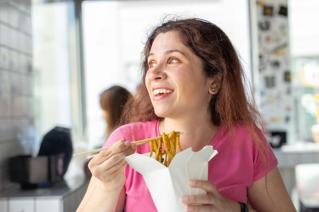 Portrait d'une jeune fille gaie mangeant des nouilles chinoises dans un café et regardant par la fenêtre. le concept de cuisine asiatique saine.