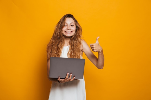Portrait d'une jeune fille gaie tenant un ordinateur portable