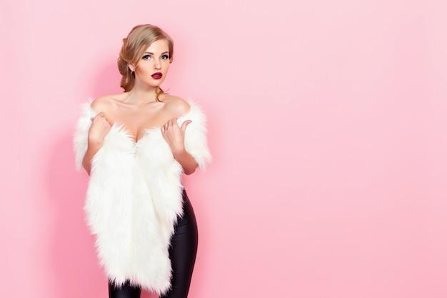 Portrait de jeune fille glamour en fourrure blanche sur rose