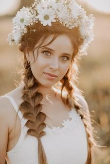 Portrait de jeune fille avec guirlande de fleurs et tresses en robe blanche dans le champ de l'été au coucher du soleil