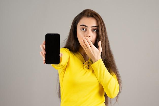 Portrait de jeune fille en haut jaune posant avec téléphone portable sur mur gris.